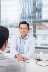 Male asian doctor comforting patient at consulting room