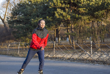 Girl roller-skating in the park at autumn. Young Asian Chinese woman in outdoor activities.