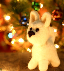 Symbol of new years 2018 white husky dog. Bolt. New years greetings background. Fancy handmade toy from wool on bokeh Christmas background. Copyspace for congratulations.
