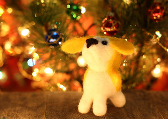 Symbol of new years 2018 yellow dog. Bolt. New years greetings background. Fancy handmade toy from wool on bokeh Christmas background. Copyspace for congratulations.