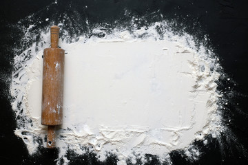 Wheat flour rolled out on a black background for text