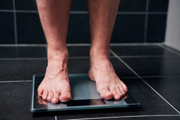 Male feet on the scale in the bathroom