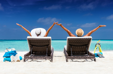 Urlaubskonzept: glückliches Paar auf Sonnenliegen streckt die Arme in die Luft am tropischen Strand