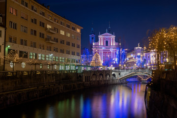 Christmas lights in Ljubljana. Franciscan Church of the Annunciation and Ljubljanica river flowing under the Triple bridge.