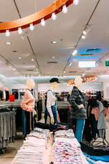 Mannequins Dressed In Female Woman Casual Clothes And Clothes On Shelves And Hanger