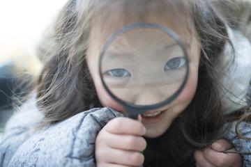 虫眼鏡で遊ぶ女の子