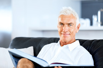 Handsome sennior man reading a book relaxing on a sofa