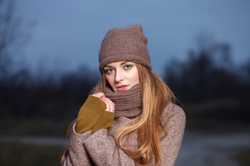 Stylish blonde woman in trendy urban outwear posing cold weather forest park. Vintage filter film saturated color. Fall mood concept.