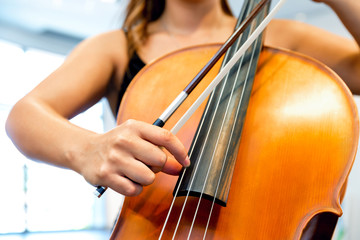 Close up of cello with bow in hands