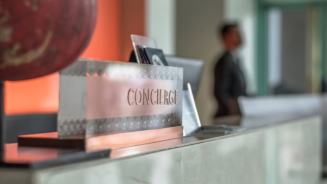 Concierge service desk counter with hotel staff team working in front of reception hall for tourist business customer