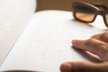 World braille day concept with blind person reading braille text touching the relief on book with finger