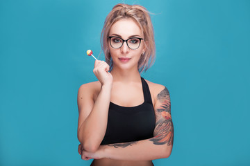 Blonde woman wearing sport outfit and glasses holding a lollipop in hands on blue cyan background