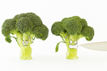Closeup of fresh green broccoli with scared cartoon style face and a sharp kitchen knife blade on white background
