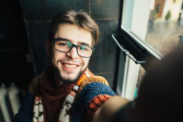 Handsome smiling hipster man blogger in glasses with beard taking selfie near window in modern loft dark interior.