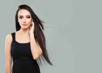 Young Perfect Woman with Long Blowing Hair and Natural Makeup on Gray Background with Copy space