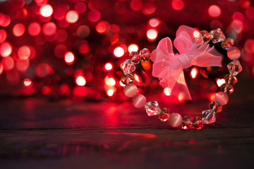 Valentine's day background.Crystal Heart with bow on background of red bokeh lights