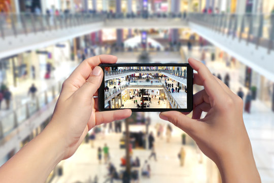 Women's hands take a picture of big mall with many people and shops on a smartphone. Picture of a lot of people in Dubai trade centre on mobile phone. Top view