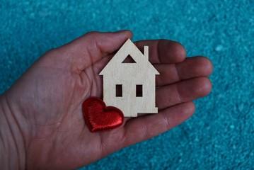 деревянный игрушечный домик и красное сердце на открытой ладони