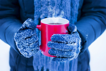 woman holding red cup with hot drink in winter