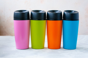 Four plastic thermos mugs on grey background