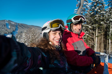 Young pair man and woman of skiers riding up on ski lift, taking selfie, smiling at the camera. Sunny day in the mountains. Close-up copyspace seasonal activity sport hobby recreation travel concept