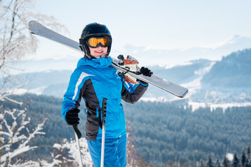 Portrait of happy female skier smiling to the camera, wearing skiing equipment, holding skis on the shoulder at winter ski resort copyspace happiness positivity vacation travelling