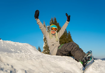 Low angle shot of a happy young woman snowboarder sitting on top of the slope, smiling to the camera, relaxing outdoors on the snow on a beautiful sunny winter day