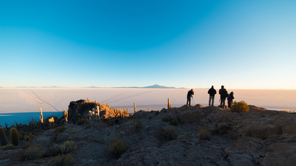 Tourists watching sunrise at Uyuni Salt Flat, travel destination in Bolivia. Wide angle shot from the summit of the Incahuasi Island.