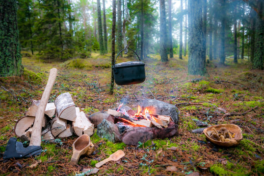 A bushcraft camp fire with hanging pot, axe and kuksa.