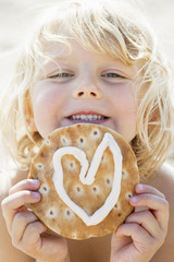 A young girl holding a pastry with heart shaped icing