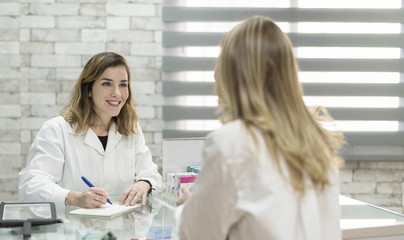 Woman customer in pharmacy with doctor woman ready for prescription