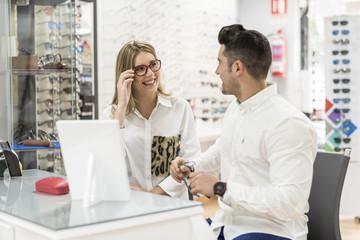 Mujer se  prueba las gafas delante de su pareja en centro optico para ver como le quedan