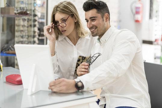 Pareja selecciona montura de gafas en tienda optica