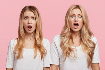 Emotional blonde young females with shocked and angry expression keep mouthes opened, being amazed to realize about loosing important beauty competition, isolated over pink studio background