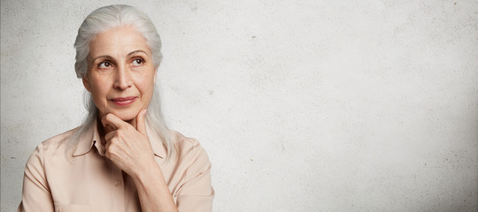 Thoughtful attractive female with wrinkled skin, remembers her youth, poses against white concrete background with copy space for your promotional text. Elderly woman thinks about something.