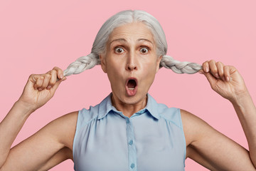 Senior shocked woman with opened mouth, keeps two pigtails, being stupefied to hear something unexpected or frightened, has crazy look, isolated over pink background. Facial expressions and emotions