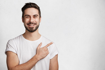 Horizontal portrait of bearded cheerful man has smile, wears casual white t shirt, indicates with fore finger at copy space for your promotional text or advertisment, isolated over concrete wall