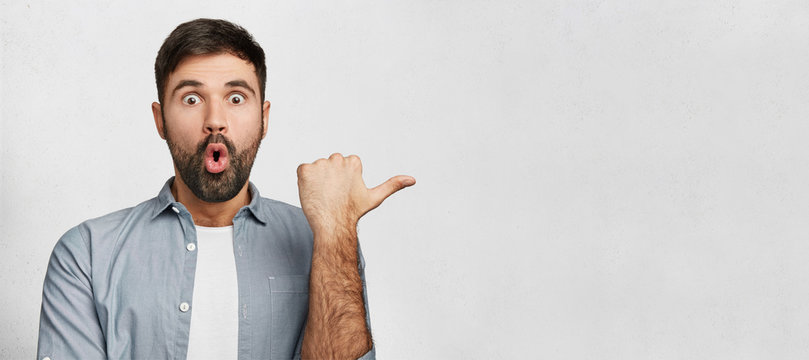 Horizontal shot of amazed young man has thick dark beard, dressed in fashionable clothes, indicates with thumb aside, shocked to notice something, copy space for your promotional text or hearder