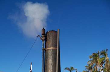 An old fashioned steam whistle blasts into a clear blue sky