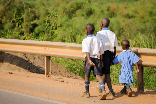 Three unidentified African Schoolchildren walking along the dangerous highway