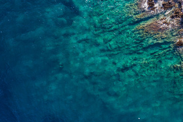 Aerial view of the green waves that beat the sea cliffs