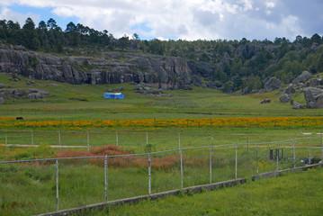 Landschaft in Mexiko in der Nähe von Creel mit hellblauem Farmhaus zwischen Feldern und vor Felsformationen