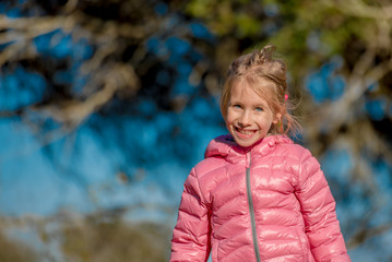 Happy little blond girl laughing, smiling in the park during sunny day