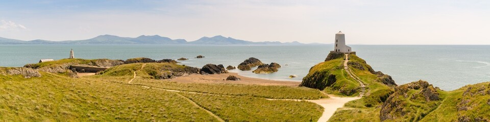 Lighthouse at Ynys Llanddwyn in Anglesey, Gwynedd, Wales, UK - with Snowdonia mountain range in the background