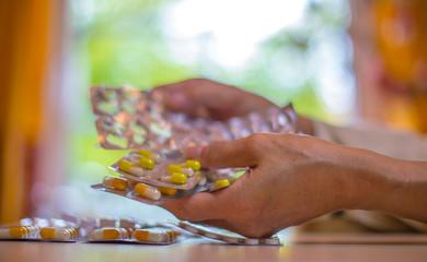 die Hände einer Frau und viele Medikamente liegen auf einem Tisch