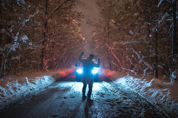 The man scared the car on the snowy road. evening night time