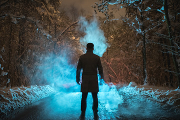The man stand near the smoke in the winter forest. evening night time