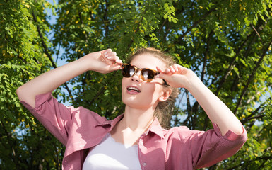 Attractive young woman in sunglasses posing in nature and clings to glasses hands