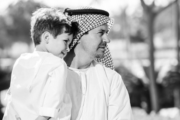 Arabic father and little kid play outdoors.