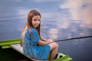 Cute child girl fishing from the shore